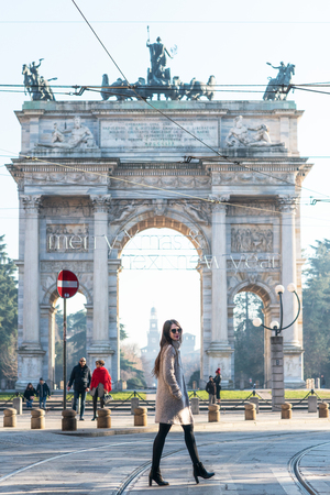 Attractive young woman wearing gray coat with long dark hair and sun glasses posing outdoor in Milan streets near  Arch of Peace, Italy. Beautiful caucasian model portrait. Street fashion 写真素材
