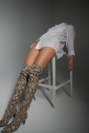 Fashion model. Young blond woman posing in studio wearing white shirt. Beautiful caucasian girl over gray background Stock Photo