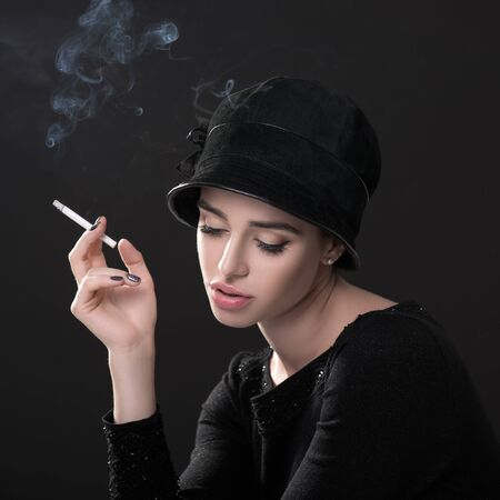 Young fashion woman smoking cigarette in hat and black drees over dark background. Vintage female portrait, styling. Image toned. Standard-Bild