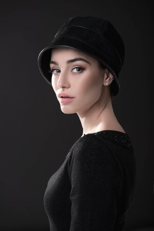Fashion woman. Black and white portrait of beautiful young elegant lady in black dress and hat. Vintage styling. Beauty, fashion, style