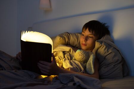 Adorable boy reads book before sleeping in bed at home with his old toy. Happy childhood.