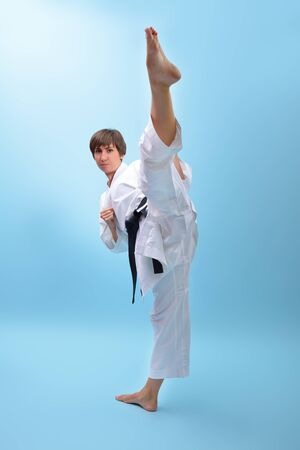 Young karate woman in a white kimono with black belt demonstrates fighting stances and strikes. Girl at studio shows martial arts
