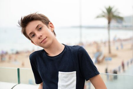 Handsome young boy looking at camera over panorama of Alicante. Beautiful calm smiling teen boy at Mediterranean coast in Spain. Travel, summer vacation, tourism, teenage lifestyle.