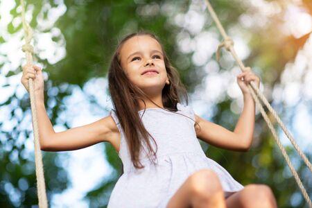 Glückliches Mädchen reitet auf einer Schaukel im Park. Kleine Prinzessin hat Spaß im Freien, Sommernatur im Freien. Kindheit, Kinderleben, Genuss, Glück. Standard-Bild