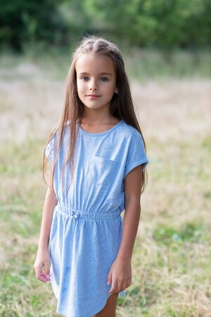 Pretty little girl posing summer nature outdoor in blue dress. Kid's portrait. Beautiful child's face