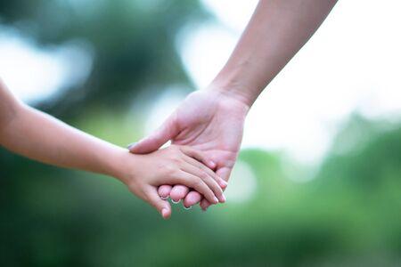 Mani di donna e bambino. La madre conduce il suo bambino, natura estiva all'aperto. Genitorialità, solidarietà, aiuto, unione, infanzia, fiducia, concetto di famiglia.