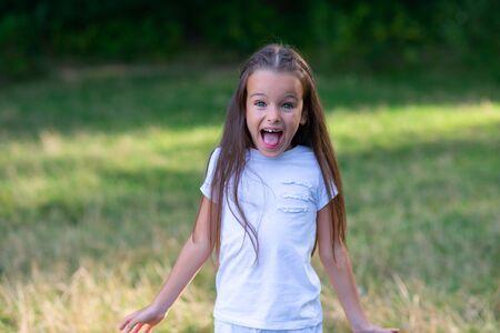 Kleines Mädchen schreit in Erstaunen, Überraschung oder Angst. Emotionales Porträt eines Vorschulkindes, Sommer im Freien