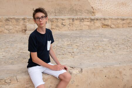Handsome young boy wearing glasses looking at camera outdoor. Beautiful calm smiling teen boy.