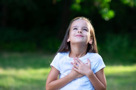 Little girl looking up to at sky with hands on chest, summer nature outdoor. Happy smiling kid feels grateful, wishes dream come true