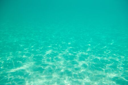 Underwater. Sun glare at the bottom of the seat. Waves underwater and rays of sunlight shining through. Deep turquoise blue sea. Ocean. Transparent water and light at sand. Stock fotó