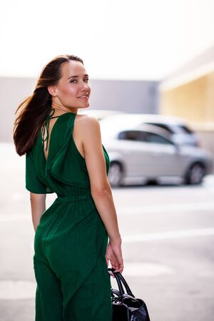 Young pretty likable cheerful woman posing summer city outdoor. Beautiful self-confident girl dressed in emerald-colored jumpsuit in house parking. Urban lifestyle