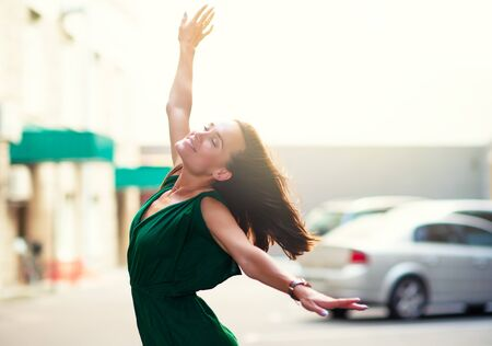 Young pretty likable cheerful woman posing summer city outdoor. Beautiful self-confident girl dressed in emerald-colored jumpsuit with long brown hair dancing enjoing life. Urban lifestyle, windy weather, image toned