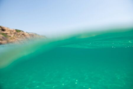 Turquoise blue sea above water surface and underwater. Sun glare at the bottom of ocean. Waves underwater and rays of sunlight shining through. Transparent water and light at sand.