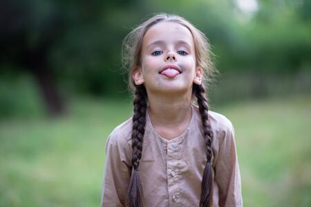 Pretty little girl with long brown hair and beautiful dirty face posing summer nature outdoor. Orphan, child of war, poor destitute kid. Small brunette with pigtails shows tongue
