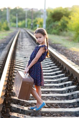 Beautiful charming little girl with pigtails dressed in dark blue dress with flowers stands at railroad with big vintage luggage. Fashion, retro stylization.