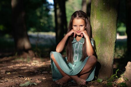 Pretty little brunette girl sitting in forest near tree with sun light at her beautiful face. Childhood. Cute kid outdoor portrait.