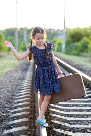 Beautiful charming little girl with pigtails dressed in dark blue dress with flowers walks on rails with big vintage luggage. Fashion, retro stylization. Stok Fotoğraf