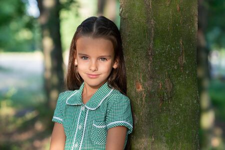 Pretty little brunette girl in forest near tree with sun light at her beautiful face. Childhood. Cute kid outdoor portrait.