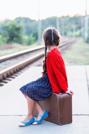 Beautiful charming little girl with pigtails waiting for train at station dressed dark blue dress with flowers and red blouse sitting on big vintage luggage. Young traveler, retro stylization. Stock fotó