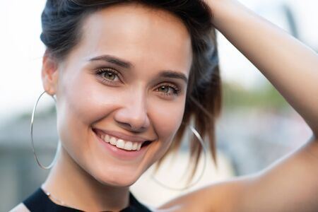 Young attractive woman with perfect smile, summer outdoor portrait. Charming cheerful girl smiling and looking at camera. Beautiful female face.
