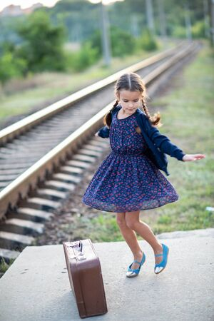 Beautiful charming little girl with pigtails waiting for train at station dressed dark blue dress with flowers and blouse and dancing next to big vintage luggage. Young traveler, retro stylization, soft focus Stok Fotoğraf