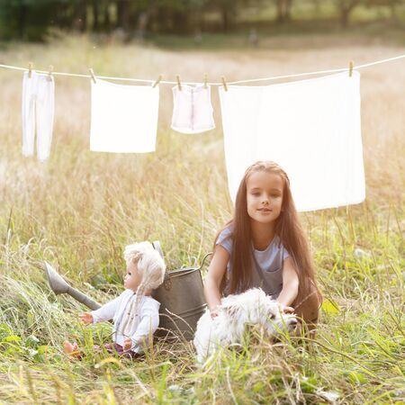 Little girl wash retro doll clothes and playing with her funny puppy, summer nature outdoor. Washing, childrens games, kids leisure, pet, play with dog, vintage style.