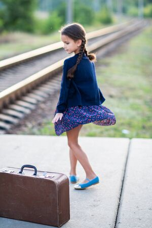 Beautiful charming little girl with pigtails waiting for train at station dressed dark blue dress with flowers and blouse and dancing next to big vintage luggage. Young traveler, retro stylization. Cute kid outdoor portrait