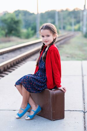 Beautiful charming little girl with pigtails waiting for train at station dressed dark blue dress with flowers and red blouse sitting on big vintage luggage. Young traveler, retro stylization.