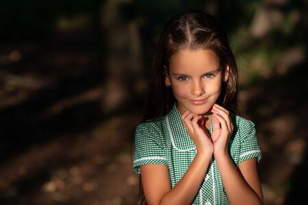 Pretty little brunette girl posing in forest near tree with sun light at her beautiful face. Childhood. Cute kid outdoor portrait. Stok Fotoğraf