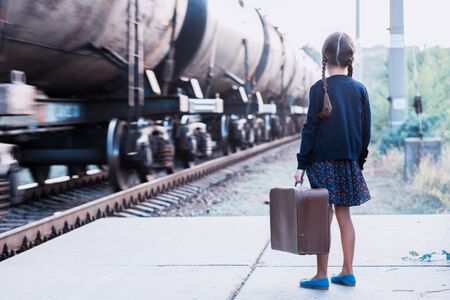 Beautiful charming little girl with pigtails waiting for train at station dressed dark blue dress with flowers and blouse holding big vintage luggage. Young traveler, retro stylization. Cute kid outdoor portrait