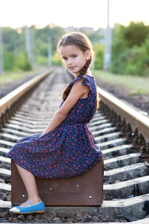 Beautiful charming little girl with pigtails dressed in dark blue dress with flowers and blouse sitting in big vintage luggage at railroad and happy smiling. Fashion, retro stylization. Stok Fotoğraf