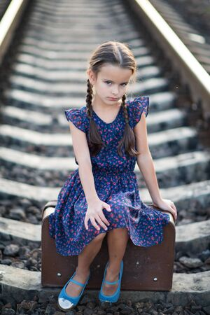 Beautiful charming little girl with pigtails dressed in dark blue dress with flowers and blouse sitting in big vintage luggage at railroad. Fashion, retro stylization. Stok Fotoğraf