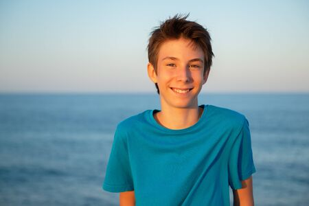 Handsome young boy at beach. Beautiful calm smiling teen boy at Mediterranean sea coast. Travel, summer vacation, tourism, teenage lifestyle.