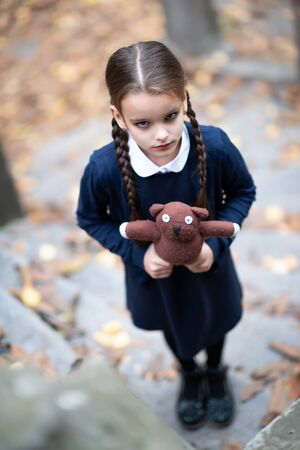 Beautiful sad little girl with with pigtails, dressed in dark blue standing near mystic abandoned building with gothic stairs and holding handmade bear toy. Halloween horror, ghost or spirit of child. Loneliness, depression Imagens