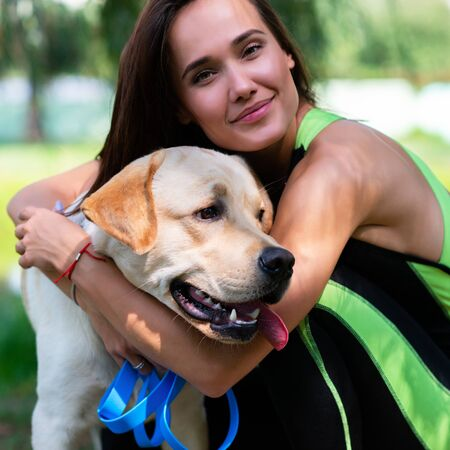 Cheerful pretty young woman sitting and hugging her dog at river bank in summer park Standard-Bild
