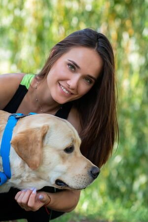 Alegre bastante joven sentada y abrazando a su perro en la orilla del río en el parque de verano Foto de archivo