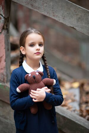 Beautiful sad little girl with with pigtails, dressed in dark blue standing near mystic abandoned building with gothic stairs and holding handmade bear toy. Halloween horror, ghost or spirit of child. Loneliness, depression