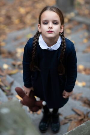 Beautiful sad little girl with with pigtails, dressed in dark blue standing near mystic abandoned building with gothic stairs and holding handmade bear toy. Halloween horror, ghost or spirit of child. Loneliness, depression Foto de archivo