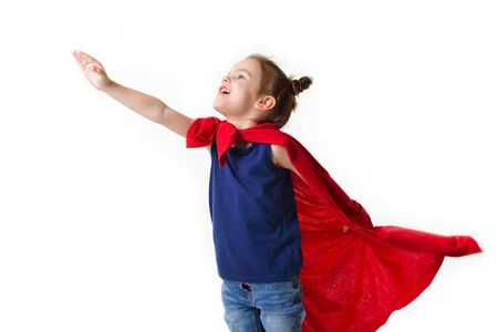 Adorable little girl flying like a superhero in blue t-shirt and red mantle. Super girl. The new generation saves the world. Good triumphs over evil. Funny kid portrait
