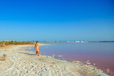 Woman wearing elegant summer dotted dress walking at bang of salty pink lake with crystals of salt. Extremely salty pink lake, colored by microalgae with crystalline salt depositions in Torrevieja, Spain