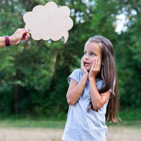 Pretty surprised thinking little girl posing summer nature outdoor with cloud of thoughts (like in comic book). Kids portrait. Emotions, feeling and thoughts of child Banco de Imagens