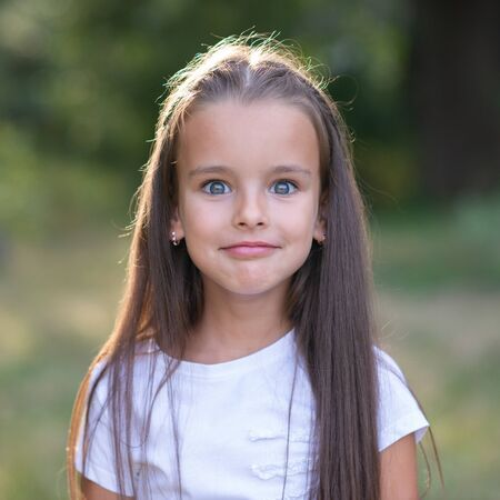 Surprise. Pretty funny little girl with long brown hair posing summer nature outdoor. Cute kid's portrait. Beautiful child's face. Facial expressions.
