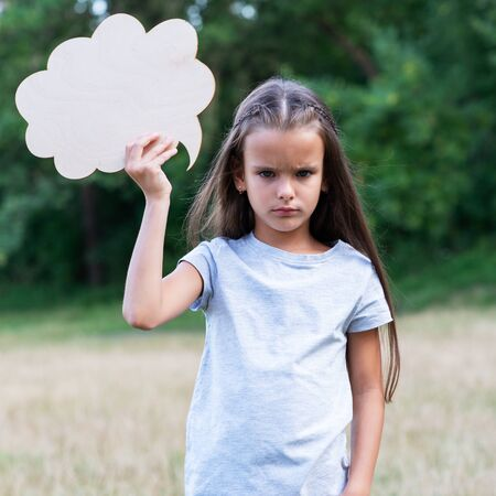 Pretty angry sad thinking little girl posing summer nature outdoor with cloud of thoughts (like in comic book). Kids portrait. Emotions, feeling and thoughts of child