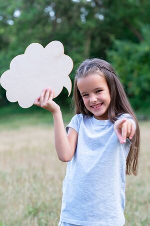 Pretty happy smiling thinking little girl pointing with her finger at camera, summer nature outdoor with cloud of thoughts (like in comic book). Kids portrait. Emotions, feeling and thoughts of child