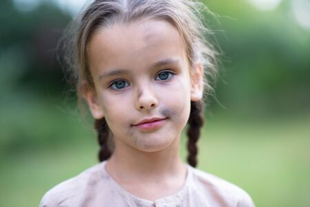 Pretty little girl with long brown hair and beautiful dirty face posing summer nature outdoor. Orphan, child of war, poor destitute kid. Small brunette with pigtails and blue eyes smiling Imagens