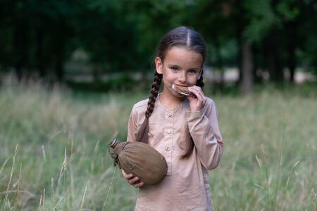 Pretty little girl with long pigtails and beautiful dirty face sitting walking in summer forest and meadow holding a piece of stale bread and vintage flask. Orphan, child of war, poverty, hunger, famine, poor destitute kid.