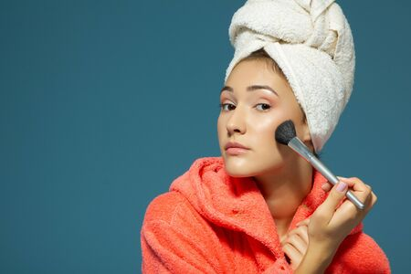 Young attractive woman putting blush on her cheekbones over blue background. Charming girl makes morning beauty treatments and make-up Foto de archivo