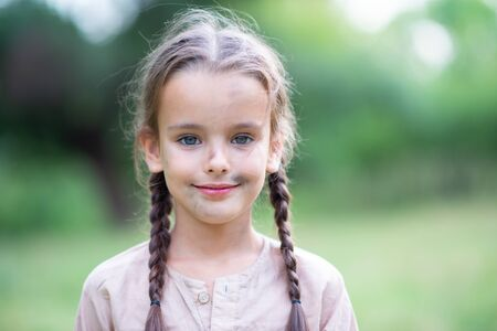 Pretty little girl with long brown hair and beautiful dirty face posing summer nature outdoor. Orphan, child of war, poor destitute kid. Small brunette with pigtails and blue eyes smiling