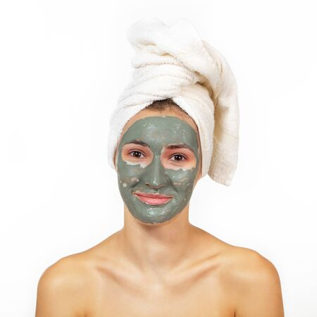 Beautiful cheerful girl applying facial clay mask. Young woman and beauty treatments over white background. Pampering, youth, anti-aging, body care spa theme. Female face with cosmetics mask Banque d'images