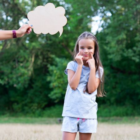 Pretty thinking little girl puts on a happy face, summer nature outdoor with cloud of thoughts (like in comic book). Kids portrait. Emotions, feeling and thoughts of child Banco de Imagens